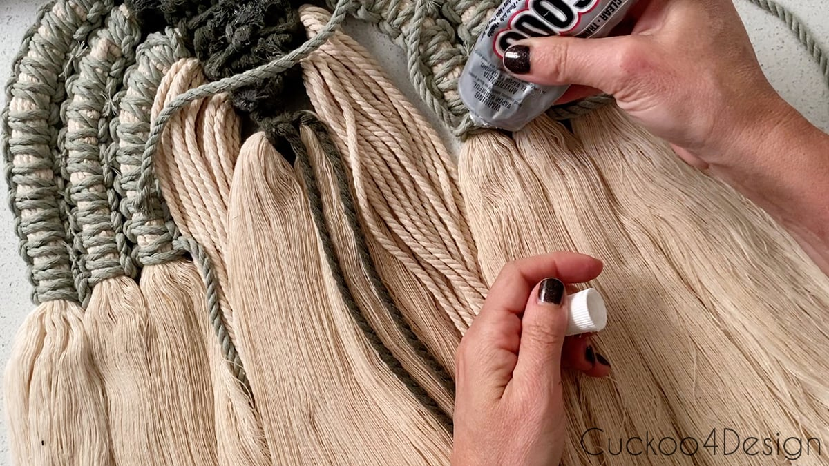 securing knots on the back of the modern macrame wall hanging with craft glue