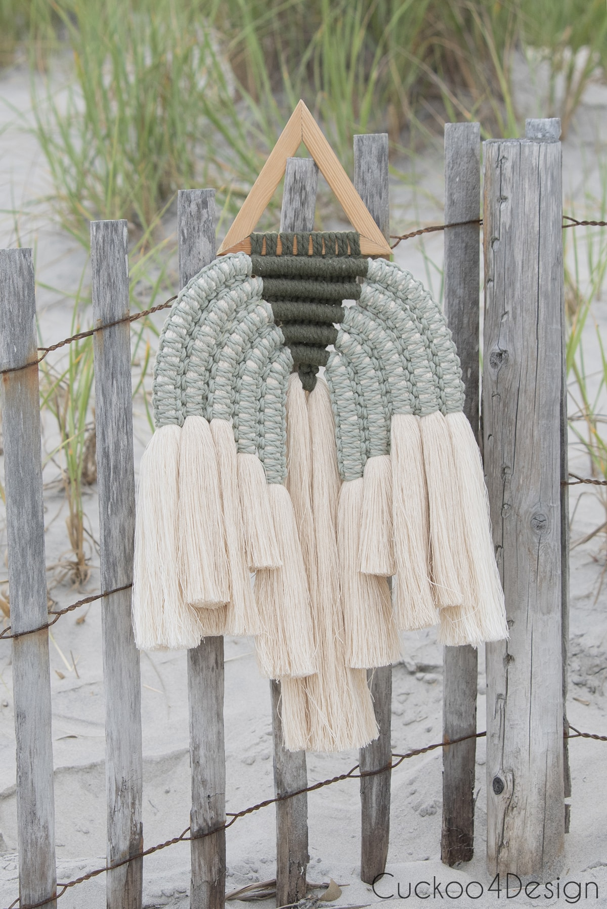 green multi-colored modern macrame wall hanging displayed on the beach