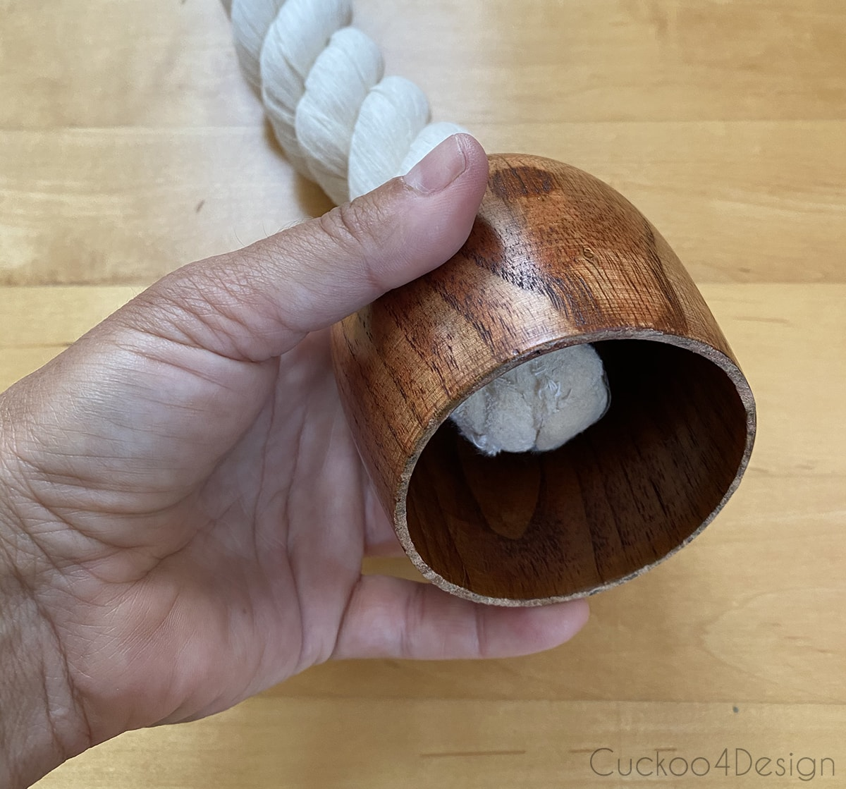 threading cotton rope through the wooden cup