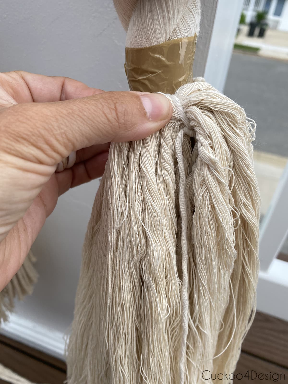 tying a knot around macrame yarn sections