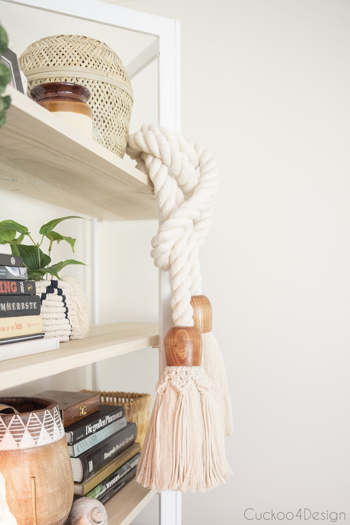 my large DIY rope tassel hanging on the made over bookshelf