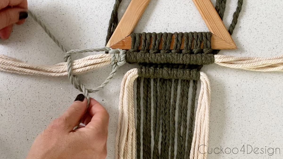 enclosing bunches of ivory macrame yarn with square knots