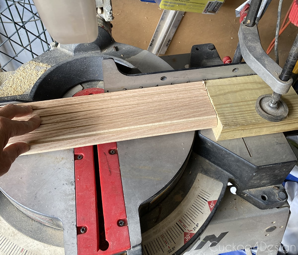 clamped piece of wood on miter saw for even length cutting
