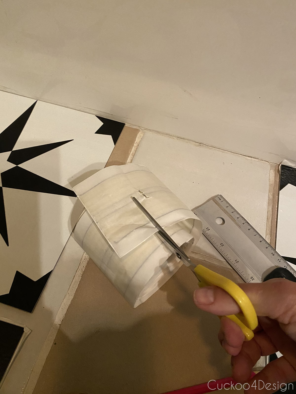 cutting double sided carpet tape to apply cheap peel and stick floor tile