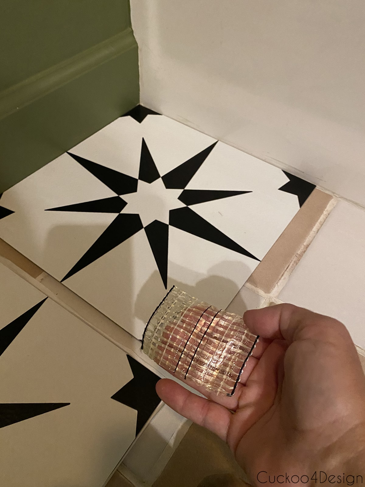 small squares of carpet tape to apply to cheap peel and stick floor tile corners