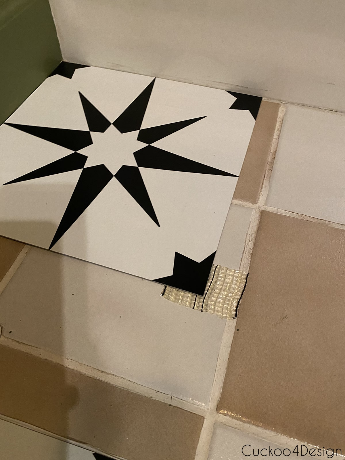 view of carpet tape applied to cheap peel and stick floor tile