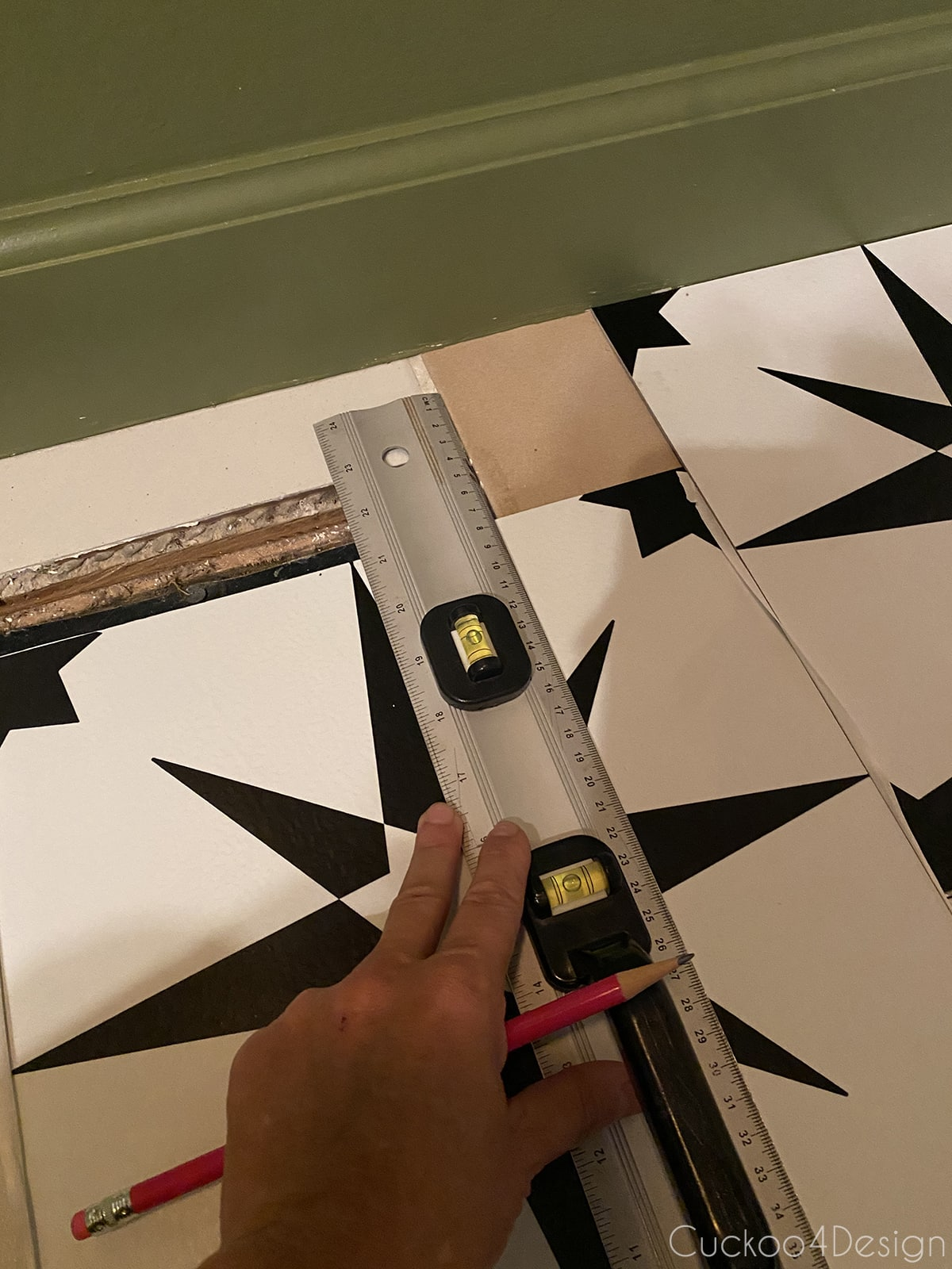using ruler and pencil to mark cuts on cheap peel and stick floor tile