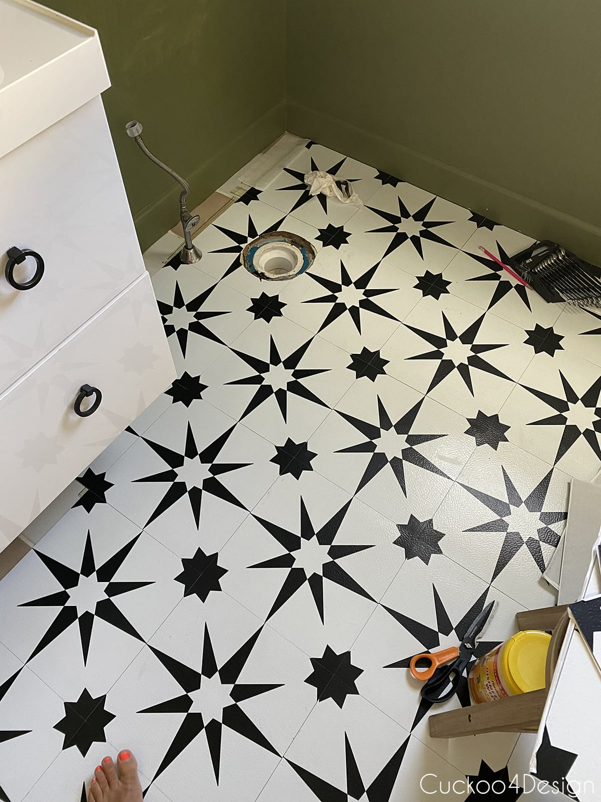 last row of cheap peel and stick floor tile behind toilet