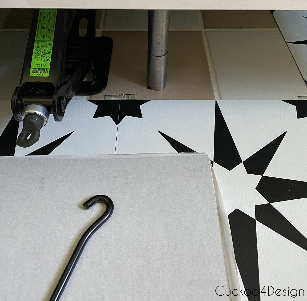 applying cheap peel and stick floor tile under Ikea floating vanity with car jack