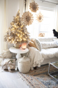 pampas grass Christmas tree in front of paper lunch bag snowflakes with lights on