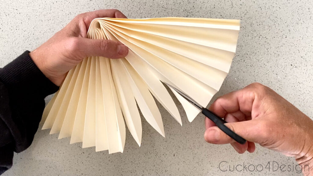cutting palm leaf details into folded paper fan