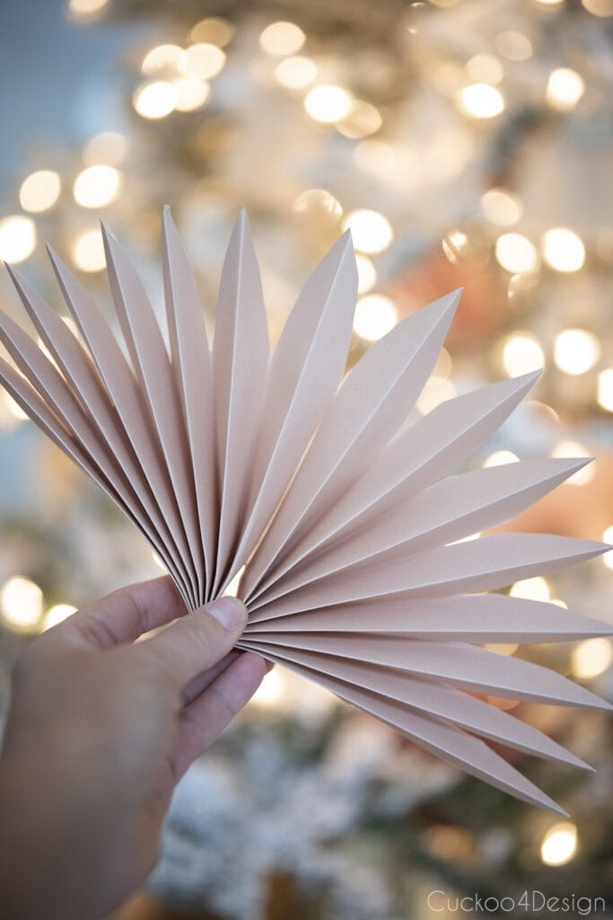 holding finished faux palm leaf paper fan decoration in hand
