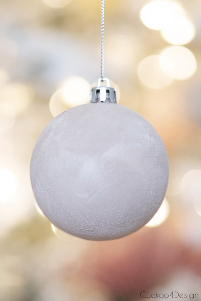 close up of cheap Christmas ornament painted to look like terracotta sphere with baking soda paint