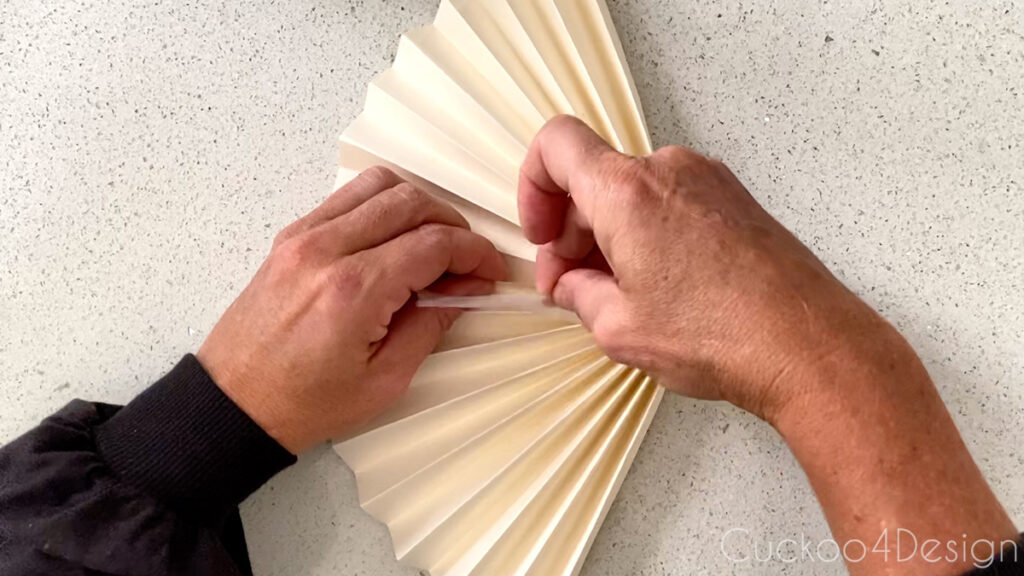 taping the folded paper fan ends together