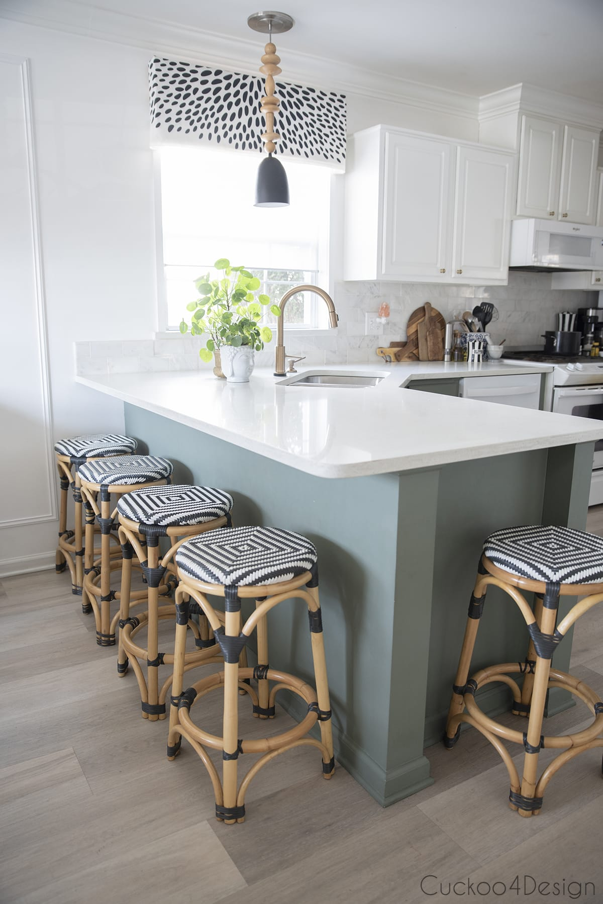 gren and white kitchen with pilea plants