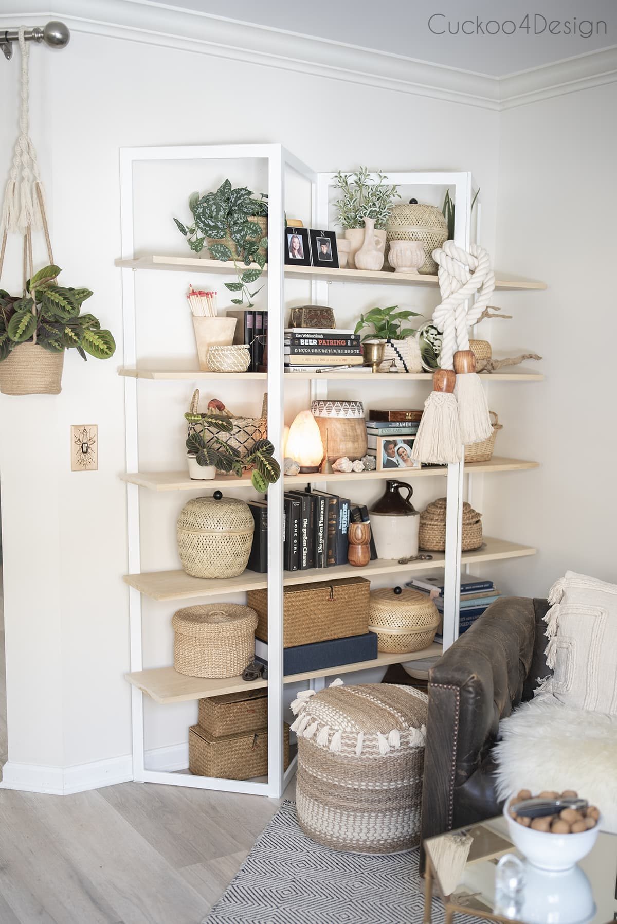 curated wooden bookshelf with beautiful house plants and new ottoman