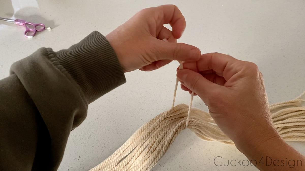 tying yarn strands in half to create tassel