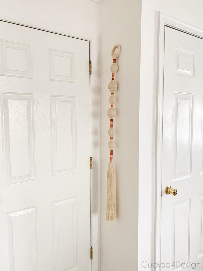 long narrow wall art tassel hanging on hallway wall