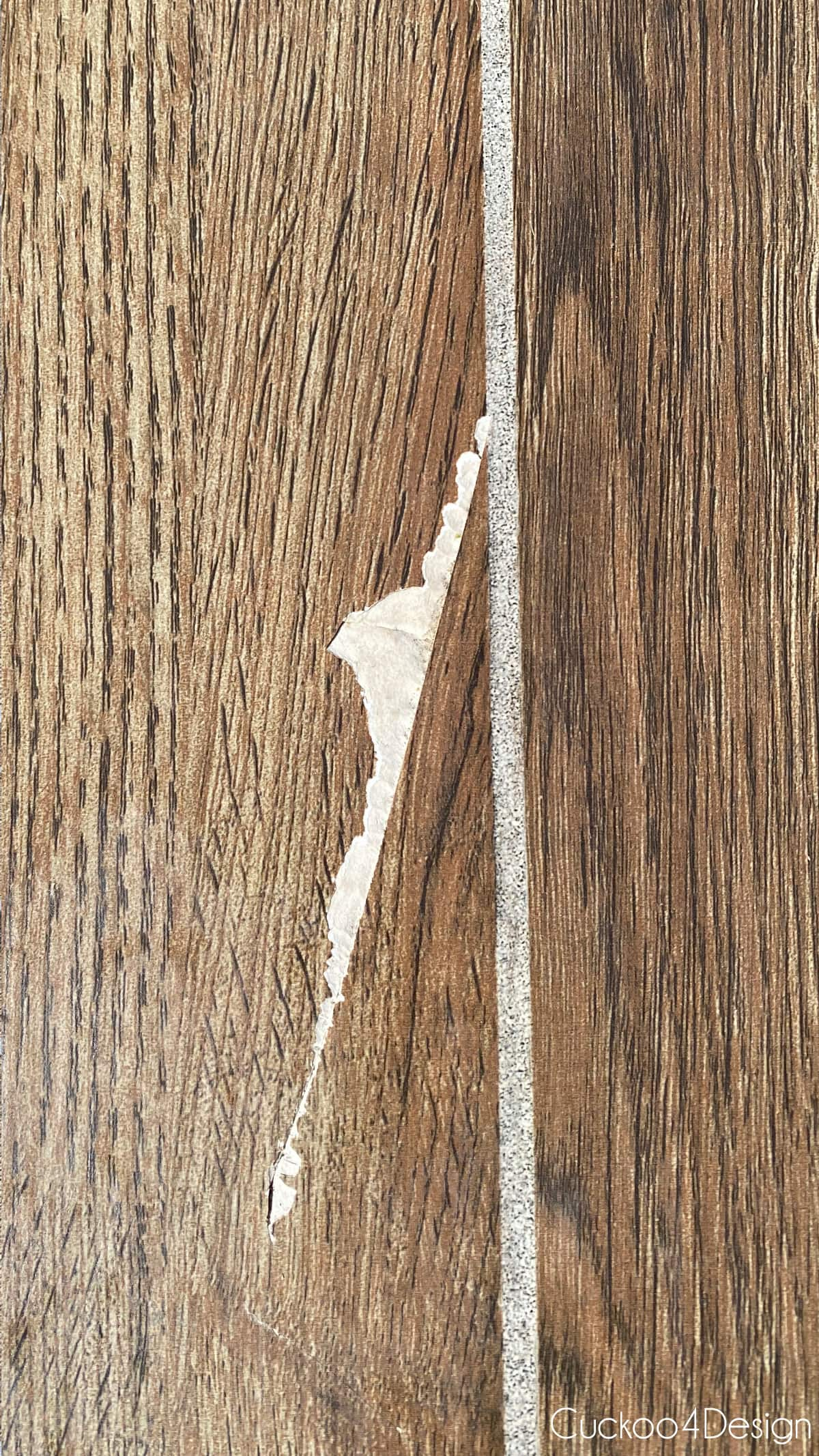 close-up view of the large chip in our wood-look tile