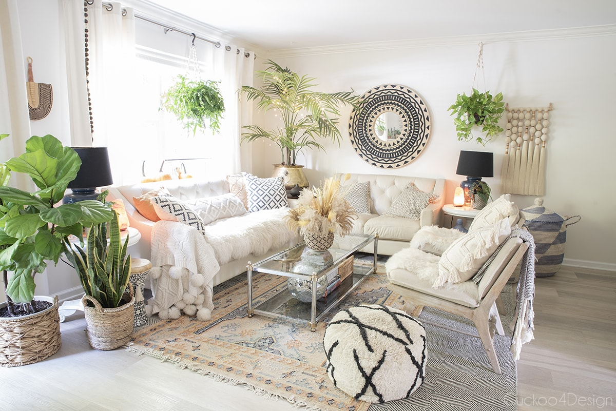 view of entire boho living room with pumpkins and fall floral arrangement